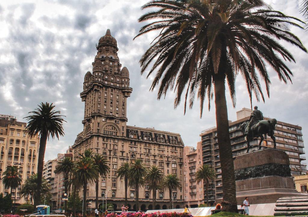 Foto panorâmica da Plaza Independencia, no centro de Montevideu. A imagem mostra edifícios ao fundo, com foco no histórico Palácio Salvo, que tem tons de bege e uma torre. Além disso, também aparecem palmeiras e um monumento em homenagem ao José Artigas