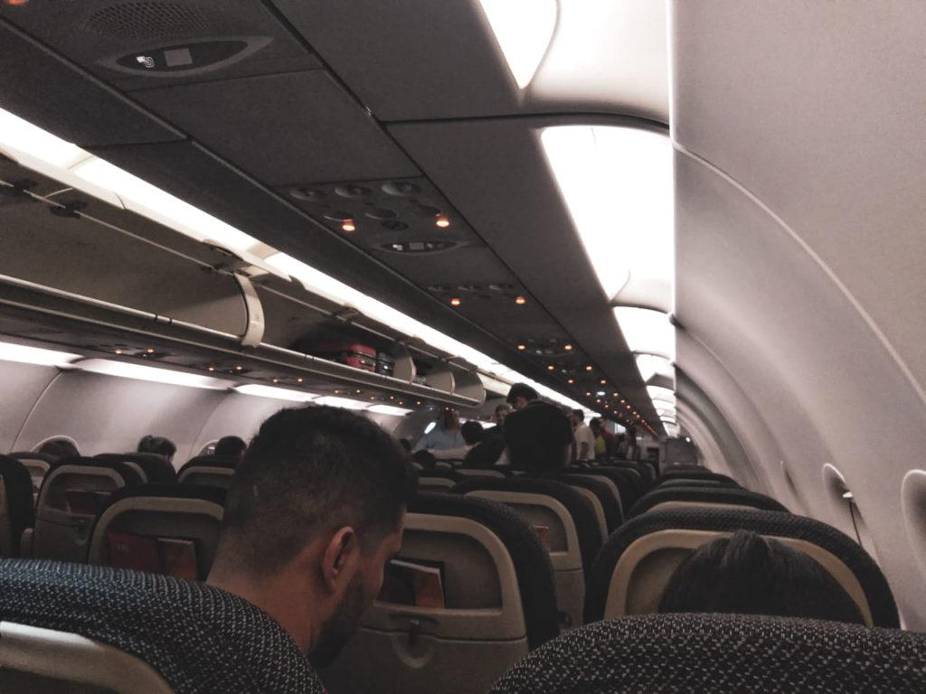 A imagem mostra o interior do avião que peguei para ir até Montevidéu. Aparecem os topos dos assentos da aeronave, os detalhes do topo do interior do avião e alguns dos passageiros