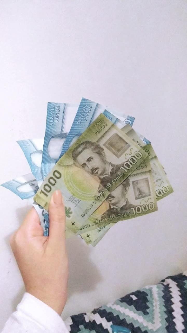 Mão segurano nove notas de pesos chilenos: cinco notas são azuis, de dez mil pesos, e quatro são verdes, de mil pesos cada. O fundo é branco
