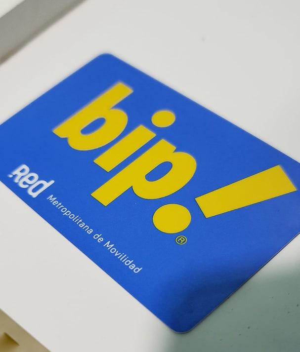 """cartão de transporte público Bip! em cima de uma superfície branca. O cartão é azul escuro e possui """"Bip"""" escrito em amarelo, bem no meio dele. Abaixo, está escrito """"Red Metropolitana de Movilidad"""" em letras brancas"""
