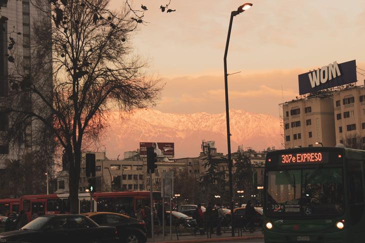 """A foto mostra o céu com algumas nuvens alaranjadas no centro e canto superior direito. No canto esquerdo, vemos a lateral de um prédio branco e uma grande árvore, que quase não apresenta muitas folhas por conta do período em que a foto foi tirada, no inverno. No centro da imagem, entre a árvore e um prédio amarelado no canto direito, vemos a Cordilheira dos Andes. Ela está iluminada e cheia de neve. Abaixo da Cordilheira, temos algumas construções mais baixas, em tons amarelados, e carros e ônibus das avenidas que percorrem o local. Há um poste bem no meio da foto e, no canto inferior direito, a frente de um ônibus verde, com o letreiro em laranja neon dizendo """"307e EXPRESO"""""""