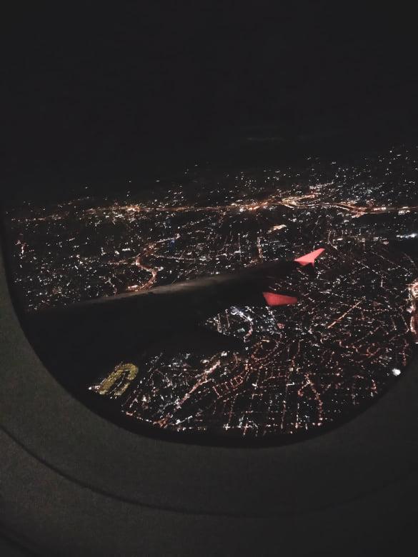 Vista da janela do avião com a asa e luzes da cidade de Santiago abaixo